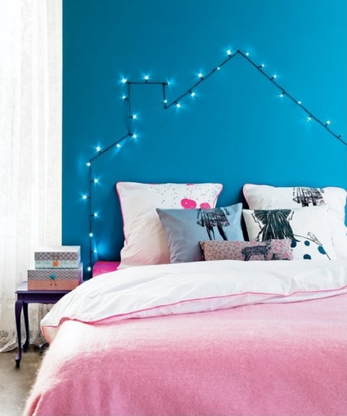 Bedroom with string light house headboard blue walls colorful bedding and pillows